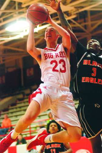 Parkersburg's Gavin Dudley sails past South Charles-ton's CJ Allison on his way to the basket during the Big Reds' 64-63 victory over the Golden Eagles Monday inside PHS Fieldhouse.   Photo by Joe Albright