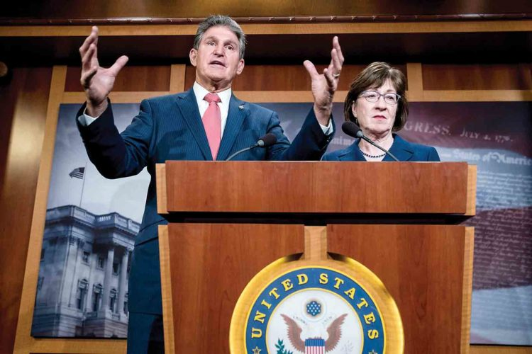 Sen. Joe Manchin, D-W.Va., left, accompanied by Sen. Susan Collins, R-Maine, right, speaks at a news conference on Capitol Hill in Washington Monday after senators reached an agreement to advance a bill ending government shutdown. (AP Photo)