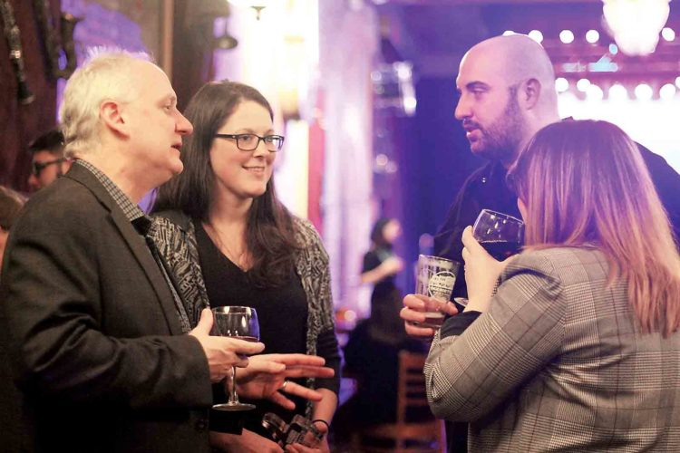 Photo by Janelle Patterson Hunt Brawley, left, Hallie Taylor, center, and Tony Styer, right, talk with Cristie Thomas, front, during the downtown celebration for Marietta Main Street Thursday at the Adelphia.