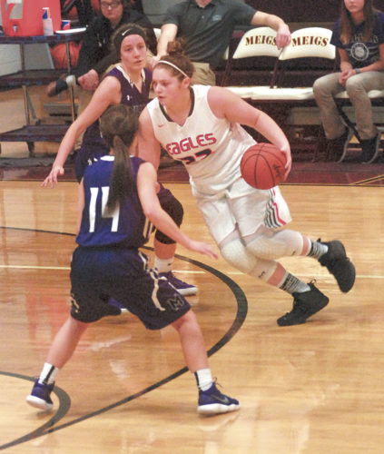 Photo by Steve Hemmelgarn Belpre's Curstin Giffin drives past Miller's Lacey Alexander (14) during the Falcons' 59-19 victory over the Golden Eagles in a Ohio Division IV sectional final.