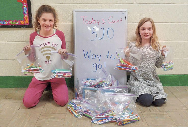 Photo by Michael Erb Criss Elementary School fourth-graders Kenslee LeMasters, left, and Alexis Starcher, right, hold up some of the more than 500 toothbrushes collected by Criss students which will be donated to children in Uganda. Students at Criss Elementary School gathered about $100 in change which will be used to purchase soccer balls for children in Uganda.