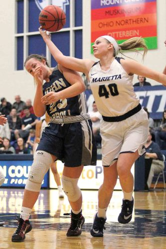 Photo by France Moise Marietta College's Corrie Burkhardt (40) tries to grab the ball during Tuesday's Ohio Athletic Conference Tournament game against John Carroll at Ban Johnson Arena.