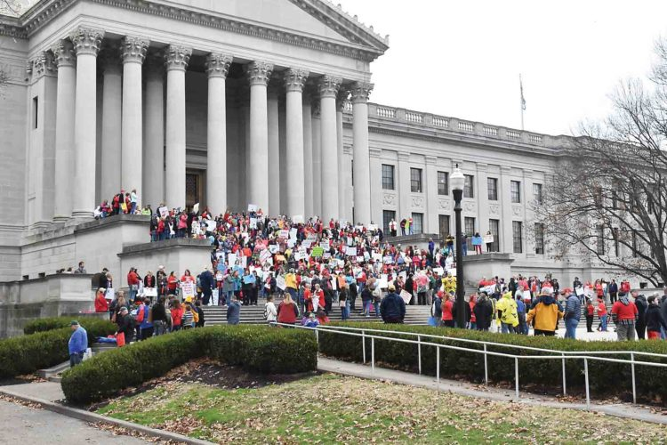 Photo by Clarissa R. Cottrill Teachers from across West Virginia gather on the steps of the state Capitol Thursday to rally for higher wages and insurance reform.