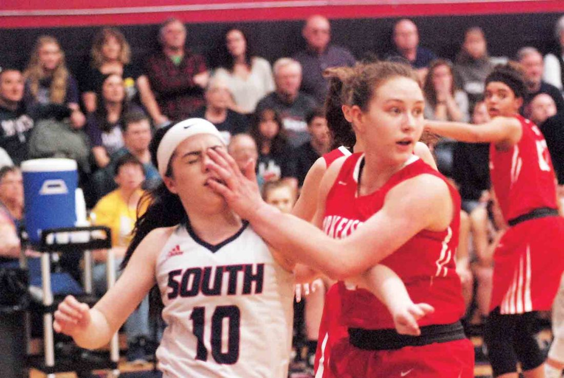 Photo by Joe Albright   Parkersburg High's Madi Mace blocks out Parkersburg South's Rylee Harner after a pass by the Patriot during South's 68-59 Class AAA Region IV, Section 1 final victory over the Big Reds Friday night at Erickson All-Sports Facility.