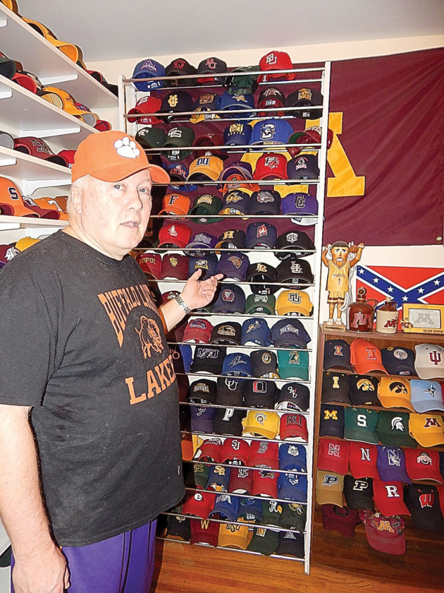 Brad Koenig looks at some of his ball cap collection.