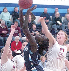 Staff photo by Steve Muscatello Minnesota Valley Lutheran's Cham Omot takes a shot between Miah Busse and Emma Jo Elder (12) of Gibbon-Fairfax-Winthrop Thursday at MVL. For more photos of this event go to cu.nujournal.com