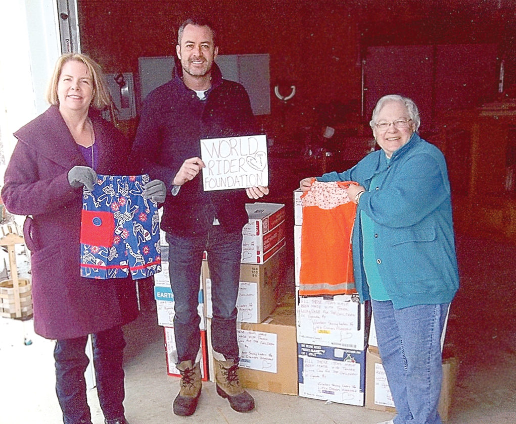CAST Director and sponsor Kathy Austinson (left) WRF Founder and CEO Mike Haley and Little Dresses manager Mary Warner prepare the boxes full of dresses for orphans in Uganda.