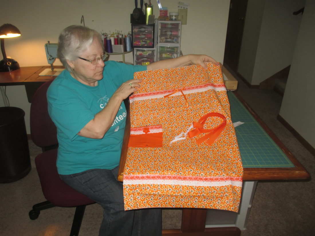 Warner show an example of the dress kits used by the sewing volunteers.