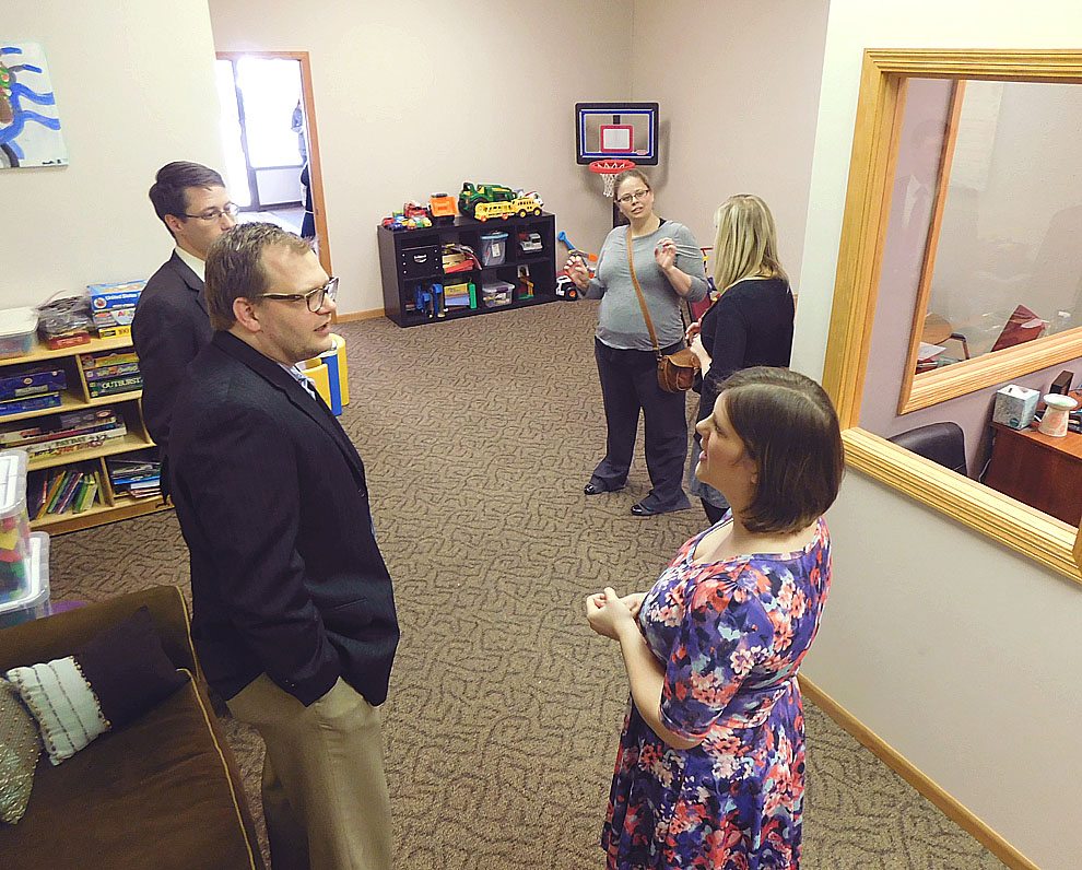 Staff phoot by Clay Schuldt CADA cutline: Mollie Beranek (bottom right corner) gives a tour of the new Keep Me Safe room at the CADA building on Minnesota Street. The Keep Me Safe room is designed a friendly-safe and education enivornment for children to meet with their non-custodial parents.
