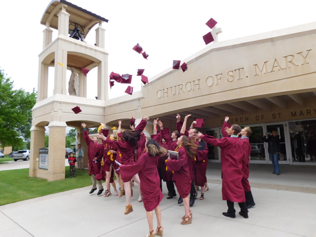 Staff photo by Clay Schuldt  Twenty burgundy mortarboard caps flew through the sky outside the Church of St. Mary Sunday afternoon, as Cathedral High School celebrated its 95th commencement ceremony.
