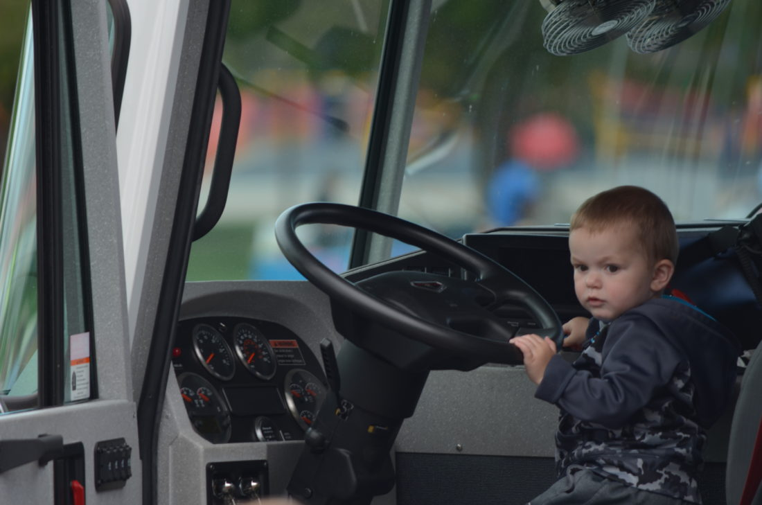 Staff photo by Connor Cummiskey  Dracen Legare, 1 1/2, sits behind the wheel of a New Ulm Fire Department pumper truck during the Early Childhood and Family Education (ECFE) vehicle fair in the parking lot at Jefferson Elementary School Wednesday.