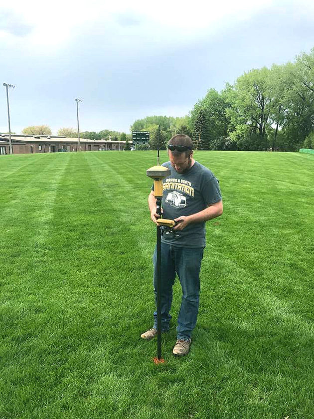 Photo courtesy of Brent Kucera Sleepy Eye St. Mary's head football coach Brent Kucera helps survey the land for the readjustment of the team's field. St. Mary's is moving down to 9-man, which requires the field to be narrowed almost 14 yards total.