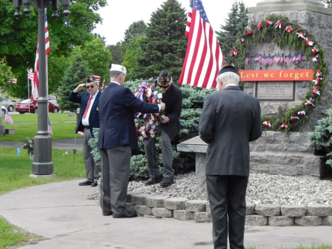 """Representatives of the American Legion Post 132 and the Veterans of Foreign Wars Post 1648 in New Ulm place a memorial wreath at the base of the """"Spirit of the American Doughboy"""" statue Sunday."""