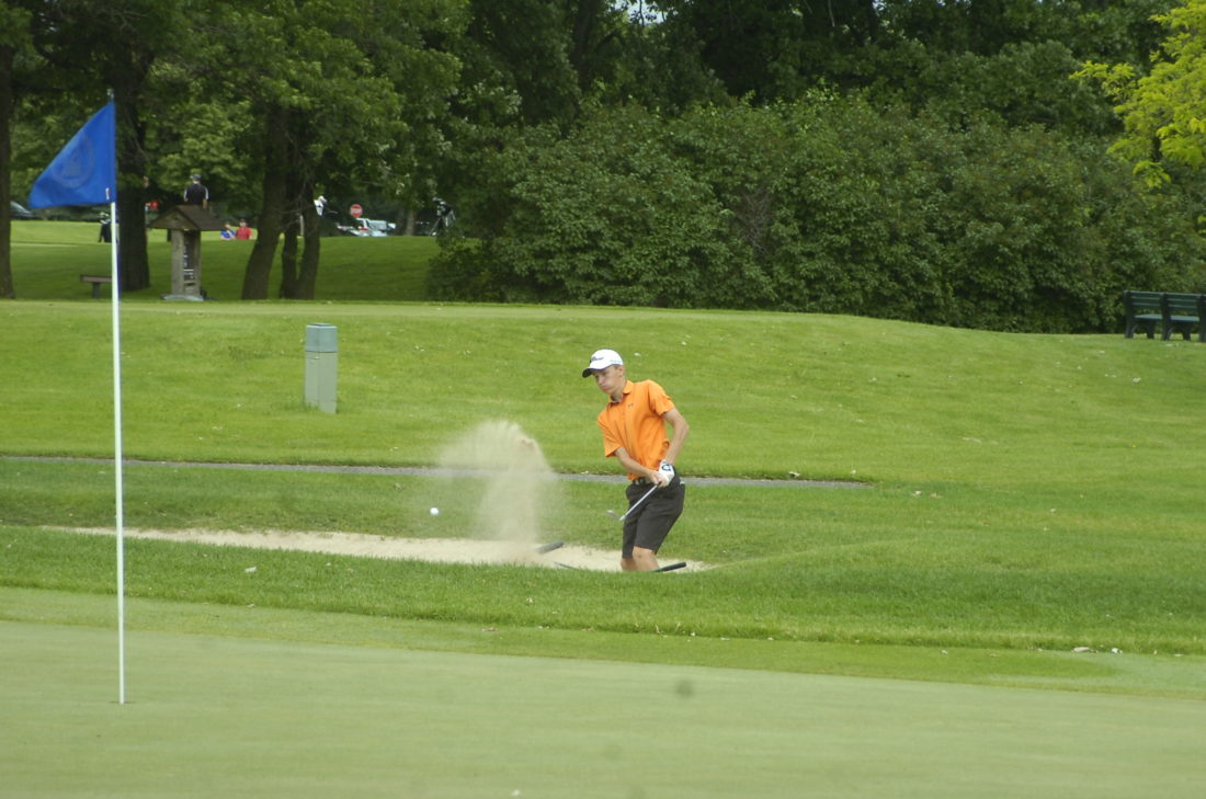 Staff photo by  Jeremy Behnke Sleepy Eye United's Caleb Christensen chips out of the bunker on Hole 5 at the Class A state golf meet in Becker.