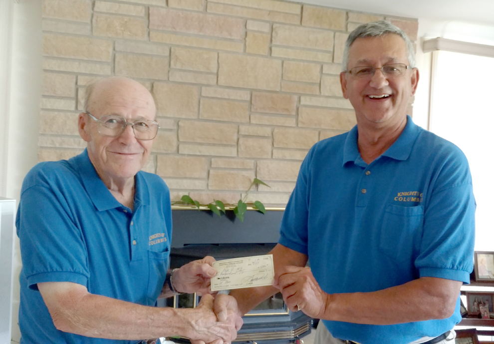 Submitted photo Local Knights of Columbus Member Nyle Mills, left, receives a $5,000 check from the Regional Consultant Lonnie Spaeth, right, after winning the grand prize in the 2017 raffle. The Minnesota Knights Foundation sponsors the raffle, offering tickets to members when they pay their dues. Half of all ticket sales go back to local councils and about $100,000 goes to the foundation's fund.