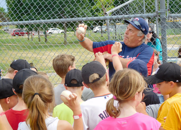 Above, Donnie Geng teaches the basics of pitching. Here he shows the students how to position the fingers on the ball in order to throw a knuckle ball.