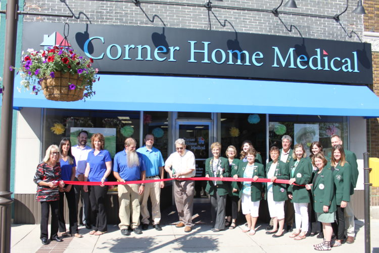 Corner Home Medical employees, from left, Gail Bjerkos, Rayna Schmid, Mike Spurling, Teresa Runge, Rhon Stuckert and Jesse Neumann, with Mayor Bob Beussman (seventh from left, with scissors) and the Willkommen Committee of the New Ulm Area Chamber of Commerce