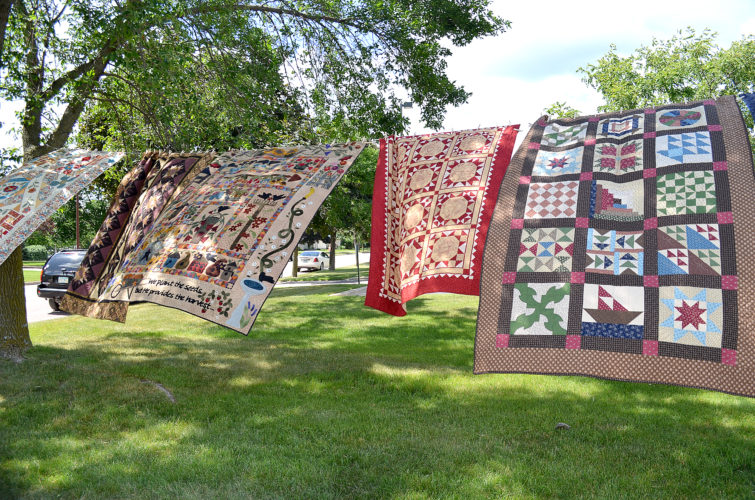 Qilts hanging from a line outside Sewing Seeds Quilt Company.