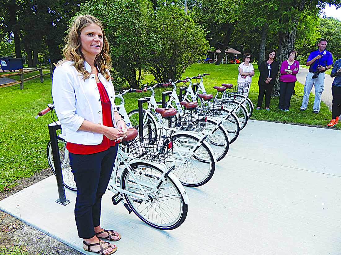 Staff photos by Fritz Busch Sleepy Eye Medical Center Community Relations Coordinator Mikayla Mages describes the new Bike Share program at Sportsmans Park Monday. Using an automated bicycle check out and return system, the seven-speed bikes are available to rent through the downloadable Movatic Rider app on an iOS or Android device.