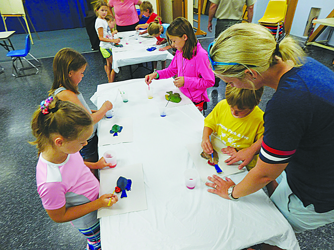 Staff photo by Clay Schuldt  Children participate in a popular fish printing exercise during a program at the New Ulm Public Library Wednesday. The children were provided with a life-size rubber mockup of a fish to paint and use as a stamp.