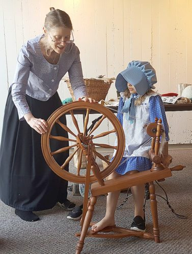 JoAnn Huss teaches the art of spinning to a young enthusiast.