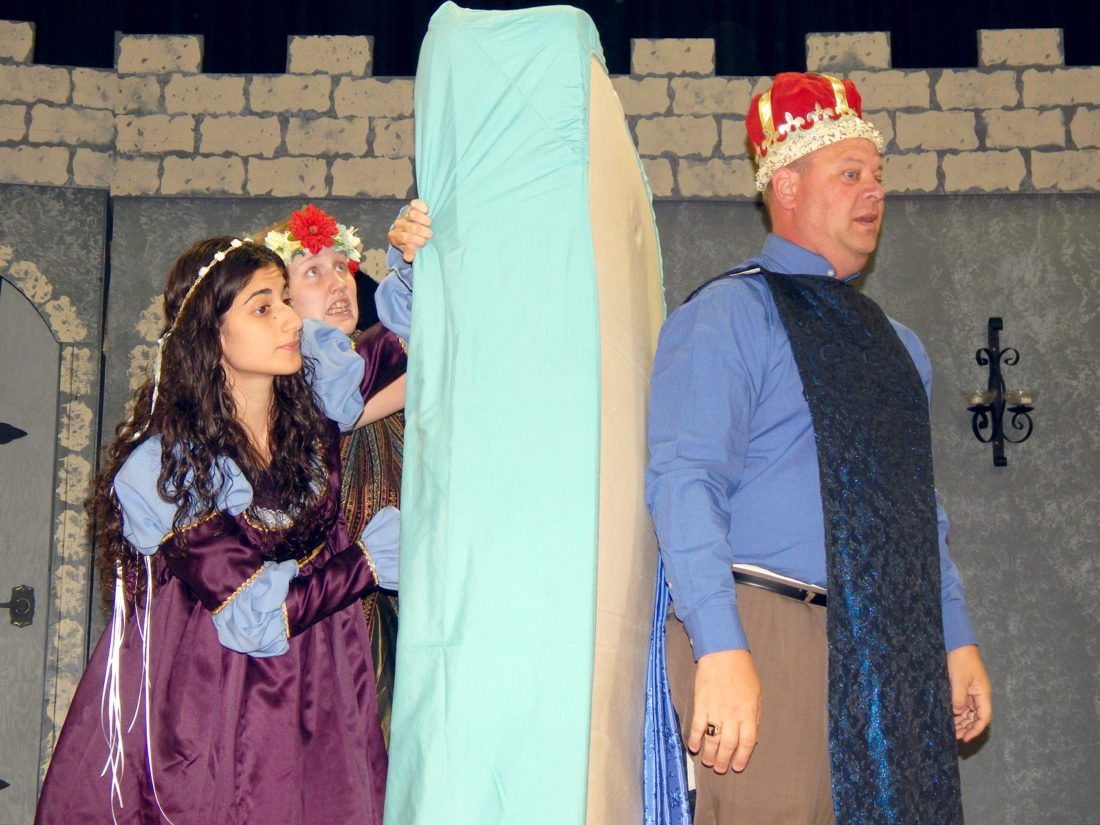 "Lady Larken (Ninah Kirchoefer) and the Minstrel (Zoe Macklanburg) hide from the queen behind a mattress as Jay Tambornino (King Sextimus) faces her in a scene from ""Once Upon and Mattress."""