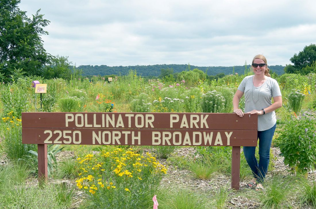 Staff photo by Connor Cummiskey The Department of Natural Resource's Regional Ecologist Megan Benage who represented the DNR on the Pollinator Park stands next to the park's sign.