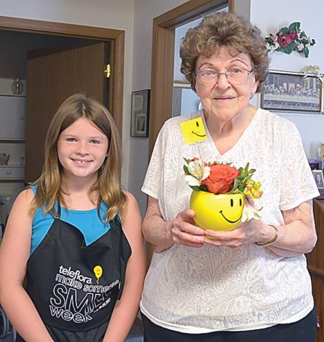 Staff photo by Connor Cummiskey Eden Isaksson, 9, (left) delivered a bouquet to Marcella Steuber (right) Tuesday at Ridgeway on German St. Isaksson was a volunteer for the Teleflora Make Someone Smile Week organized by A to Zinnia Florals & Gifts.
