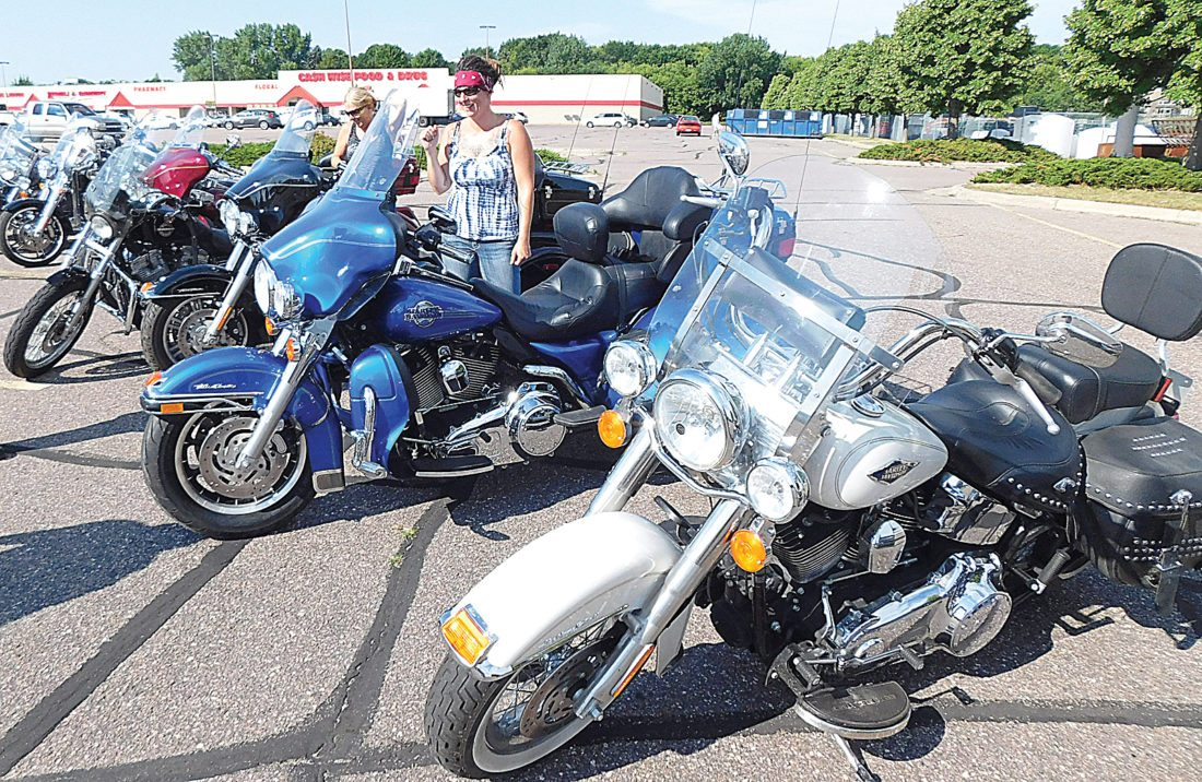 Below: Rebecca DeMarais stands among several of the group members motorcycles.