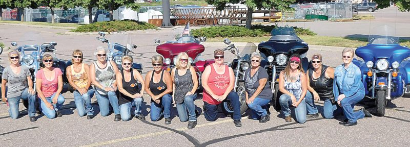 Group picture in front of Runnings sign: (Left to right) Patricia Hartman, Shellie Kahler, Judy Schewe, Shirl Huiras, Doris Loverude, Paulette Rewitzer, Phillis Lepp Annie Albaugh, Rebecca DeMarais, Gail Holm and Mary Rewitzer all pose with their bikes before their weekly ride.