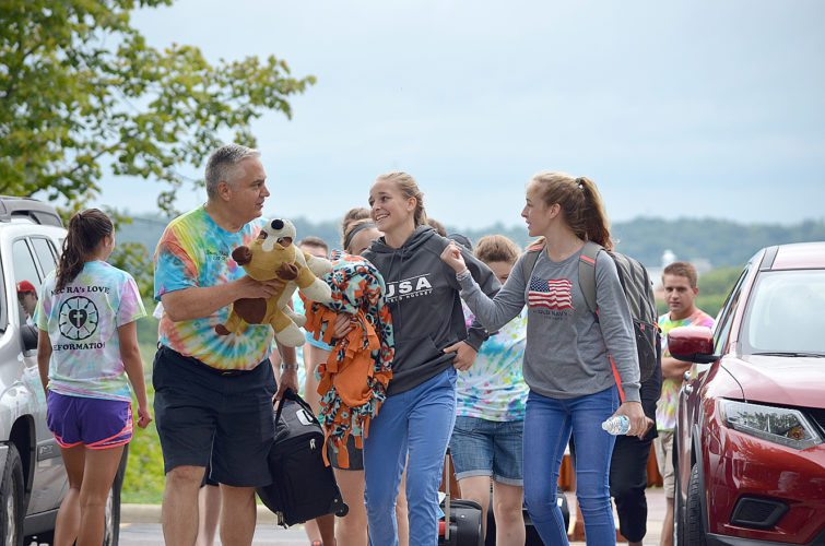 Martin Luther College President Mark Zarling (left) and Margaret Johnson (middle) help Rebecca Johnson (right), a freshman, move into Centennial Hall Thursday, during the first day regular students can move in.