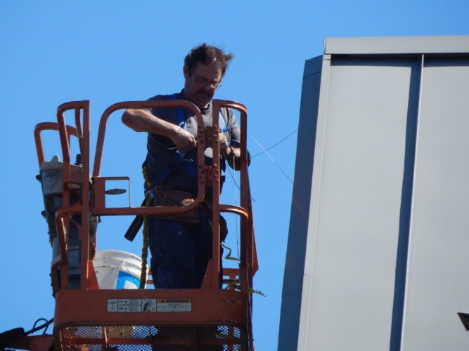 Staff photo by Fritz Busch  David Lehman installs bird deterrent netting on the south side of the Brown County Courthouse roof Tuesday.