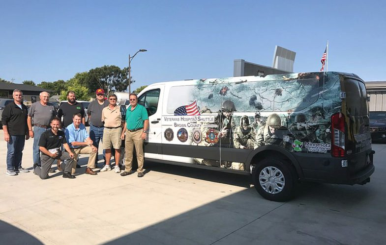 Submitted photo  Brown County Veterans Van drivers receive an orientation tour of their 2017 Transit Van at Chuck Spaeth Ford. Pictured kneeling: Mike Krueger (salesman & USMC Veteran), Greg Peterson-Service Officer. Driver�s standing L-R: Elver Niebuhr, Kevin Guggisberg, Brian Kroesch, Bill Day, Dave Janni, and Assistant Service Officer Dave Koester. The new van replaces their 2008 Sprinter which recently turned over 300,000 miles. The van picks up in Springfield, Sleepy Eye, and New Ulm and takes Veterans to VA medical care in Minneapolis and St. Cloud. The van is wrapped with a special graphics depicting conflicts from WWII to the Global War on Terror. Randy Horejsi of New Ulm designed and wrapped the van. For more information about the van and it�s use contact the Brown County Veterans Office at: 507-233-6636.