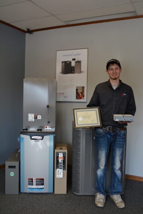 Staff photo by Connor Cummiskey  HVAC technician Seth Cordes holds his recently acquired certification for radon mitigation and one of the devices he uses to detect radon in houses.
