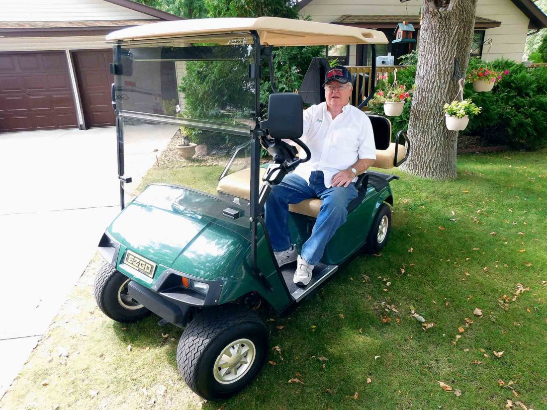 Staff photo by Clay Schuldt Bill Wolf sits in his 2002 Model EZ GO golf cart. Wolf has the distinctions of being the first person to receive a Special Vehicle permit to operate a cart in New Ulm.