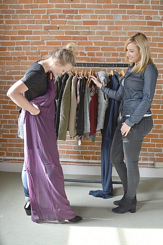Staff photo by Connor Cummiskey  Gallery 512 co-owner Jessica Fischer, left, shows Assistant Manager Bethany Hutchens, right, a purple dress that is part of the new fall collection to be modeled at the Modenschau.