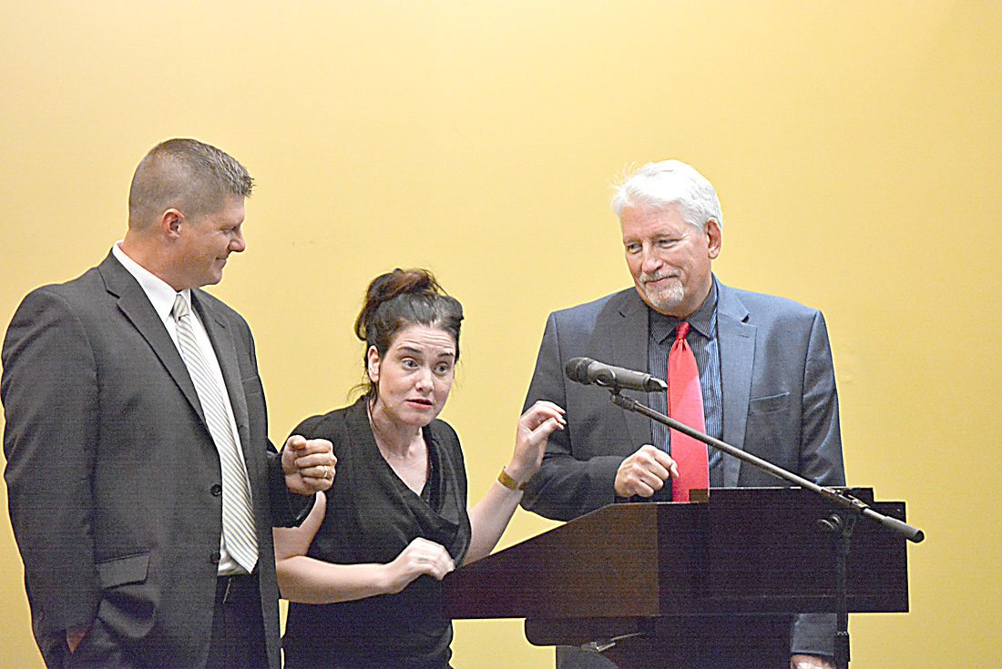 Staff photo by Connor Cummiskey  Gianna Jessen, center, an abortion survivor who lives with cerebral palsy as a result, stands with the support of Brad Finstad, left, and Glen Lewerenz, right, to address the crowd at the sold-out event at the Hero for Life Banquet Tuesday night at the New Ulm Event Center.