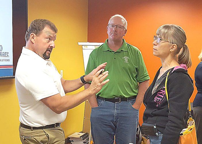 Jeff Nielsen, president and CEO of United Farmers Cooperative in Winthrop, left, explains the intricacies of 40 Square Cooperative Solutions to area agriculture producers Steve Hoffman, New Ulm, center, and Karen Lamb, Hector.  Photo by Kerry Hoffman