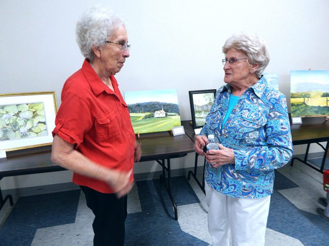 Staff photo by Fritz Busch Veronica Niehaus, left, of Sleepy Eye, talks with Sleepy Eye artist Peggy A. Tauer at her art show at the Sleepy Eye Community Center Friday. The art show with 36 of Tauer's works, continues 10 a.m to 2 p.m. Saturday. Light refreshments will be served.
