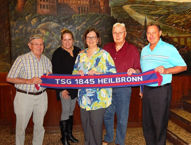 New Ulm's Turner Hall had a visitor from Germany with a gift this week. Hans Mueller, left, from Heilbronn, Germany, brought a fan scarf from the Heilbronn Turnverein's soccer club to present to the New Ulm Turners on Wednesday. Mueller has visited Minnesota many times since being an exchange student in Minneapolis in 1953, and first visited New Ulm in 2000. The gift was given in honor of William Pfaender, who was born and grew up in Heilbronn, and helped found the Heilbronn Turnverein in 1845 before coming to the U.S. and helping found New Ulm. Accepting the gift are (from left Virginia Suker Moldan, Turner Hall manaager; Yvonne Weber, Ed Weber, and David Hirth,  members of the Turner Hall board of directors.