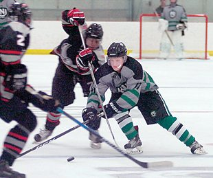 Staff photo by Steve Muscatello New Ulm Steel forward Jack Parks tries to get through a pair of Willmar Warhawks players during the first period Saturday at the New Ulm Civic Center. For more photos of this event go to cu.nujournal.com