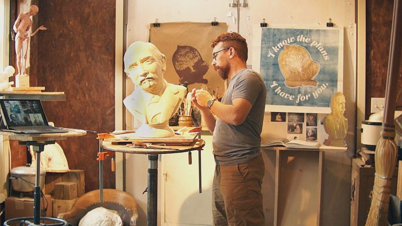 NUCAT image from video Jason Jaspersen works on clay mold of Julius Berndt in this still shot from the second episode of the Process. The acorn print in the background was created in the first episode.