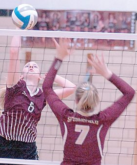 Staff photo by Steve Muscatello New Ulm Cathedral's Mary Herzog spikes the ball over Katelynn Clemson (7) of Springfield Tuesday at CHS. For more photos of this event go to cu.nujournal.com