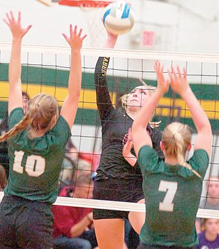 Wabasso's Amanda Hoffman spikes the ball between Mallory Helget (10) and Ali Beltz (7) of Sleepy Eye St. Mary's Tuesday in Sleepy Eye. For more photos of this event go to cu.nujournal.com