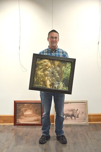 Staff photo by Connor Cummiskey  Artist Todd Jacobs holds a picture of a lion he took in Kenya while getting ready to set up his show in the 4 Pillar Gallery.