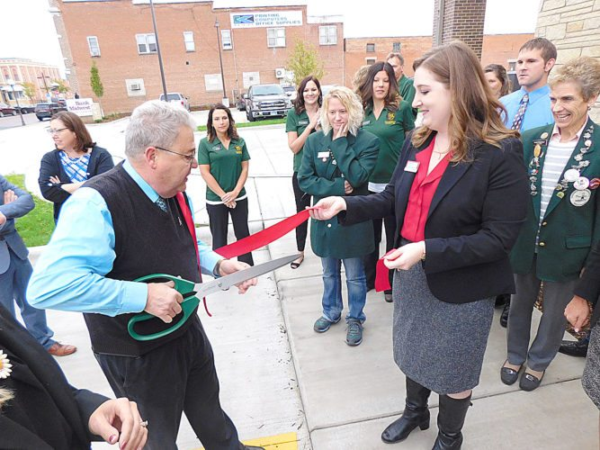 Staff photo by Clay Schuldt  Mayor Bob Beussman (foreground, left) cuts the ceremonial ribbon at Bank Midwest Thursday as Jessica Janni holds the other end of the ribbon.