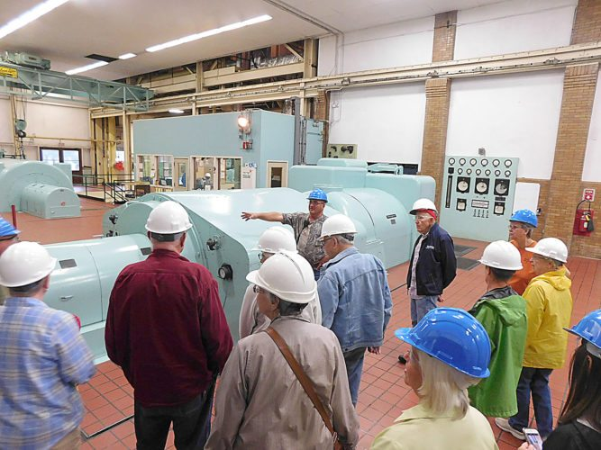 Staff photo by Clay Schuldt  Dave Kuehn (back, center) leads a tour of the New Ulm Public Utilities Power Plant. Tours of the facility were held throughout the day to promote Public Power Week. Kuehn estimated over 60 people viewed the plant. This year the focus of Public Power Week was on the steam heating system. Visitors to the plant were able to see the steam system and ask questions about its operation.