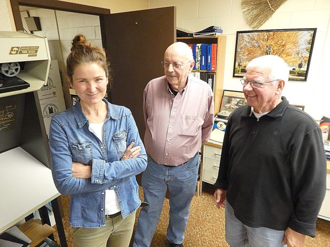 Staff photo by Fritz Busch  German author Marion Hahnfeldt, left, visits the German-Bohemian Society (GBS) Library-Resource Center Thursday. GBS members President Patrick Eckstein, center, and original board member Elroy Ubl, right, greet her.