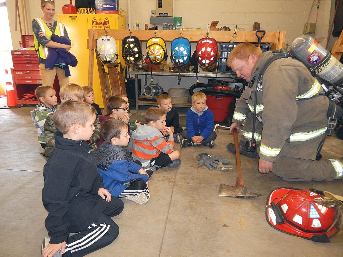 New Ulm firefighter Trent Zabel describes firefighting gear to Jefferson Elementary School students during their tour at the Engine House No. 1 open house Wednesday. It's Fire Prevention Week through Oct. 14.