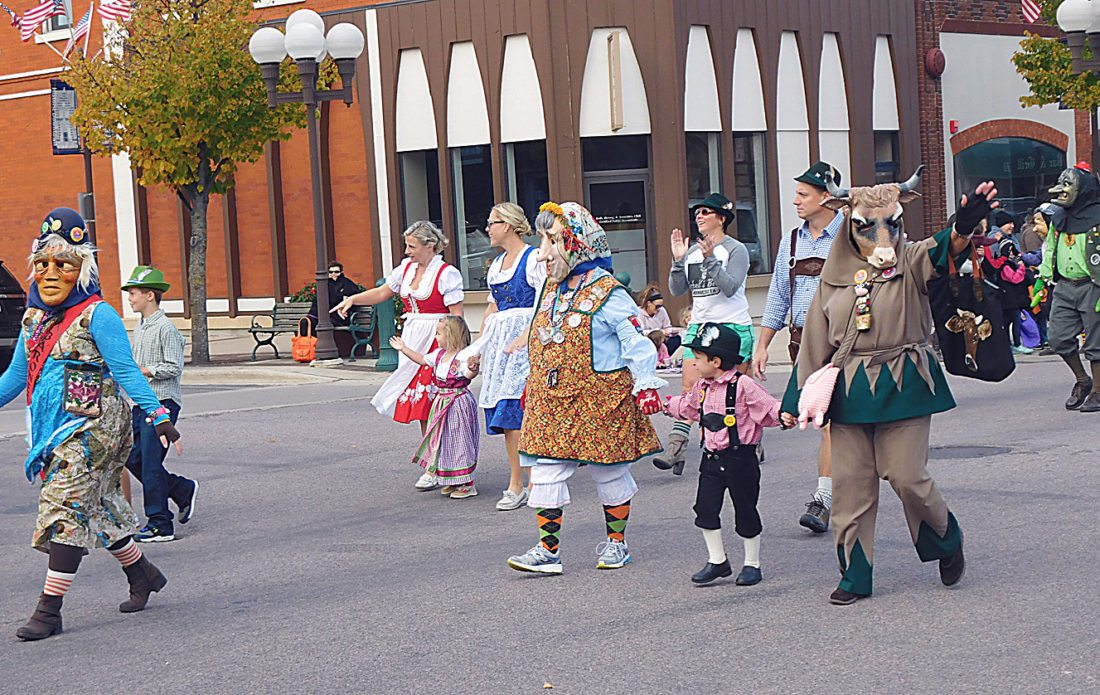 Staff photo by Clay Schuldt The Narren walk the Oktoberfest Promenade parade route down Minnesota Street hand in hand with local kids.